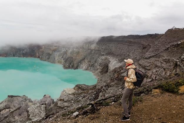 Mężczyzna turysty spojrzenia przy siarkowym jeziorem na ijen wulkanie na wyspie jawa w indonezja. wycieczkowicza mężczyzna z plecakiem podróżuje na odgórnej górze, podróży pojęcie