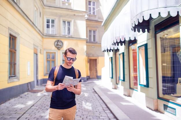 Mężczyzna turystyczny z mapą miasta i plecakiem na ulicy europy.
