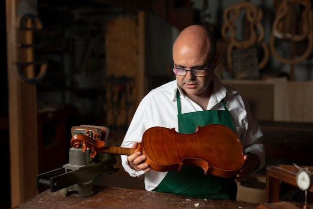 Mężczyzna tworzący instrument w swoim warsztacie