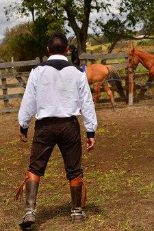 Mężczyzna ubrany do ujeżdżenia pracujący z końmi