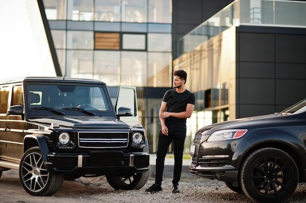 Mężczyzna ubrany na czarno pozuje w pobliżu samochodów suv