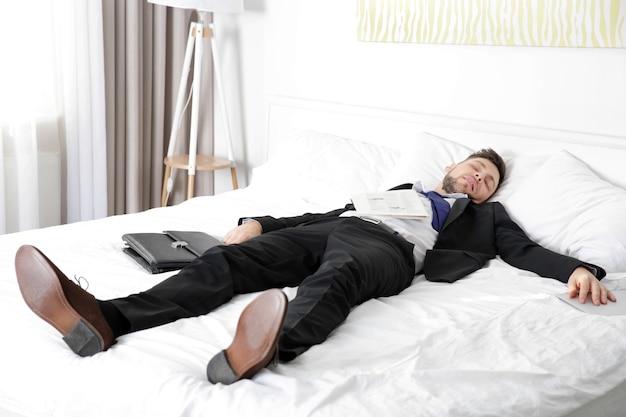 Mężczyzna ubrany w biznesowy garnitur zasnął na łóżku w jasnym pokoju