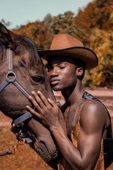 Mężczyzna ubrany w brązowy kapelusz kowbojski i przytulanie konia