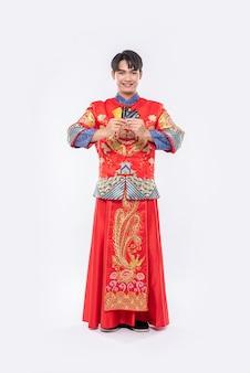 Mężczyzna ubrany w cheongsam ma przy sobie kilka kart kredytowych na zakupy podczas chińskiego nowego roku.