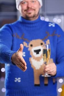 Mężczyzna ubrany w ciepły niebieski sweter z jeleniem trzyma w ramieniu