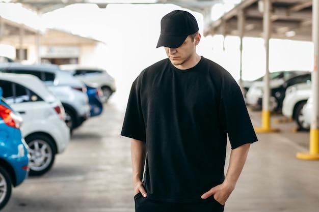 Mężczyzna ubrany w czarną koszulkę i czarną czapkę z daszkiem na parkingowym tle