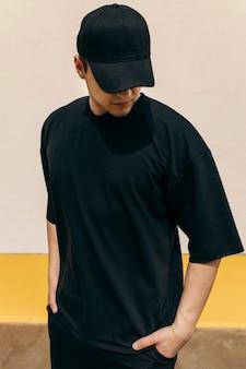 Mężczyzna ubrany w czarną koszulkę i czarną czapkę z daszkiem na tle ściany na zewnątrz