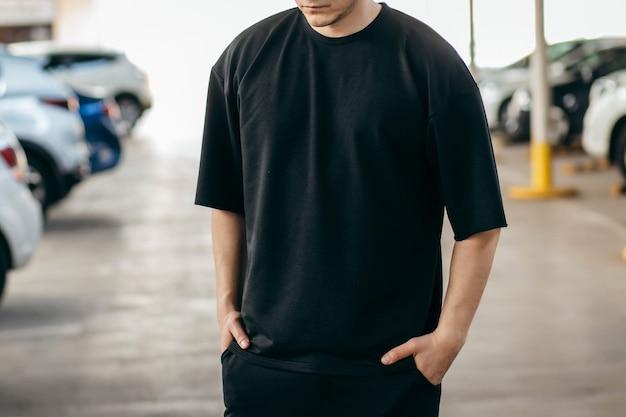 Mężczyzna ubrany w czarną koszulkę na parkingowym tle
