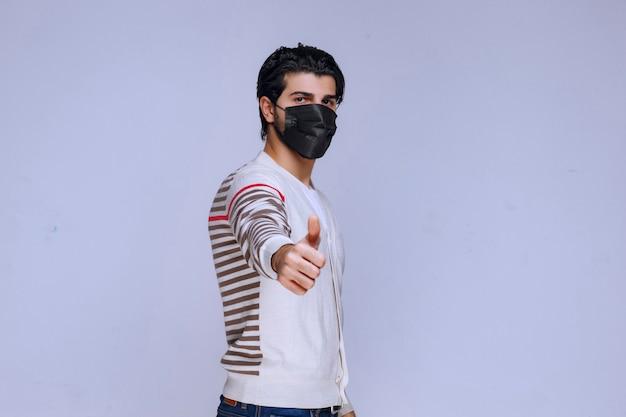 Mężczyzna ubrany w czarną maskę i robiący kciuk do góry.