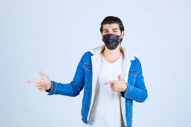 Mężczyzna ubrany w czarną maskę i wskazujący na lewo.