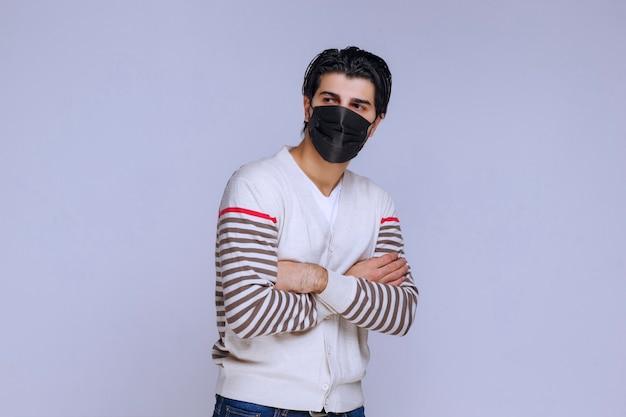 Mężczyzna ubrany w czarną maskę krzyżującą ramiona.