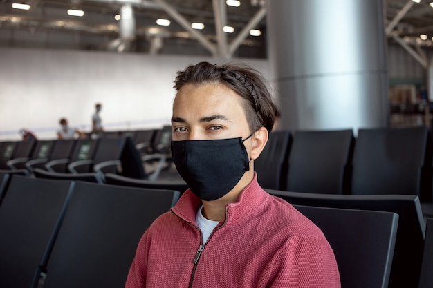 Mężczyzna ubrany w czarną maskę ochronną na lotnisku.
