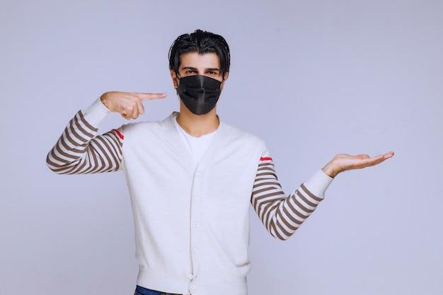 Mężczyzna ubrany w czarną maskę, przedstawiający coś w ręku.