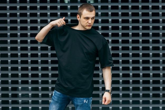 Mężczyzna ubrany w czarną pustą koszulkę z miejscem na logo lub projekt mock up