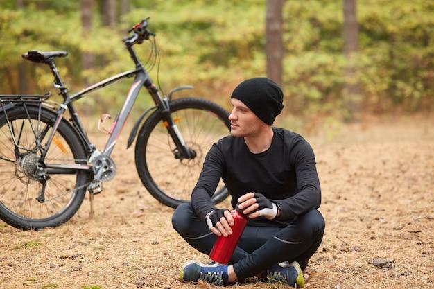 Mężczyzna ubrany w czarny dres i czapkę siedzi onground ze skrzyżowanymi nogami w pobliżu swojego roweru, rowerzysta przestaje pić wodę