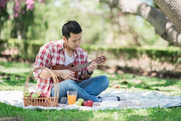 Mężczyzna ubrany w czerwoną koszulę, grając na ukulele i czytając książkę