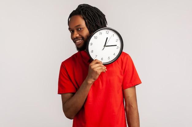 Mężczyzna ubrany w czerwoną koszulkę w stylu casual, trzymający zegar, uśmiechający się do kamery