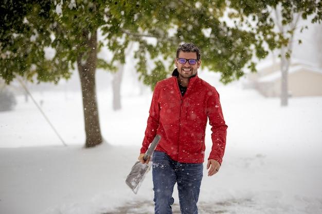 Mężczyzna ubrany w czerwoną kurtkę i idący po zaśnieżonym polu, trzymając łopatę do śniegu