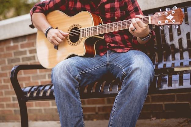 Mężczyzna ubrany w czerwono-czarną flanelę siedzi na ławce, gra na gitarze