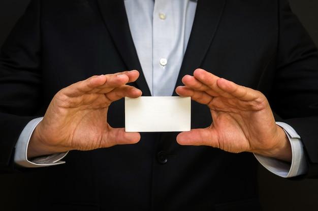 Mężczyzna ubrany w garnitur, trzymając białą wizytówkę na czarnej ścianie