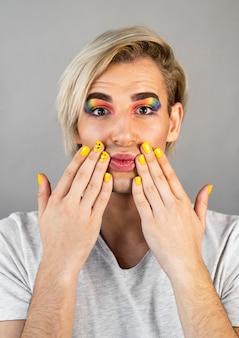 Mężczyzna ubrany w kosmetyki do makijażu i lakier do paznokci