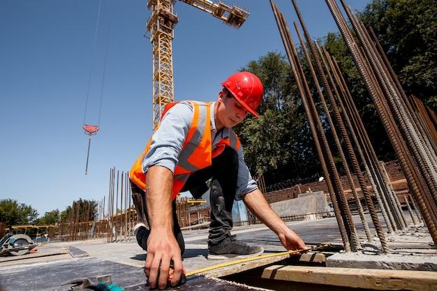 Mężczyzna ubrany w koszulę, pomarańczową kamizelkę roboczą i kask mierzy taśmą mierniczą dziurę na placu budowy. .
