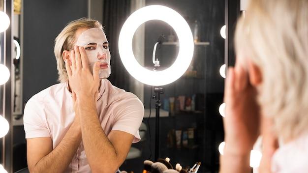 Mężczyzna ubrany w makijaż stosując maseczkę na twarz