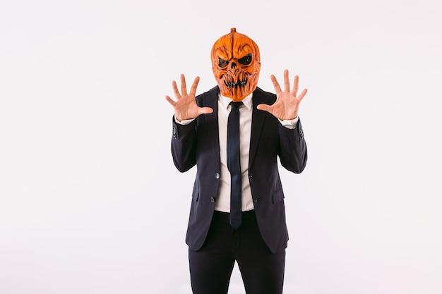 Mężczyzna ubrany w marynarkę, niebieski krawat i maskę z dyni jack-o-lantern straszy rękami. koncepcja uroczystości halloween i karnawał.