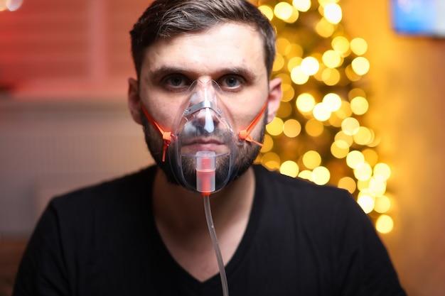 Mężczyzna ubrany w maskę do inhalacji płuc przed lampkami choinkowymi