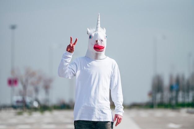 Mężczyzna ubrany w maskę jednorożca robi gest zwycięstwa palcami