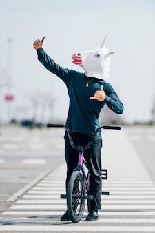 Mężczyzna ubrany w maskę jednorożca robi zdjęcie smartfonem