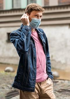 Mężczyzna ubrany w maskę medyczną na zewnątrz