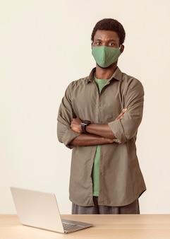 Mężczyzna ubrany w maskę medyczną stojący obok swojego laptopa