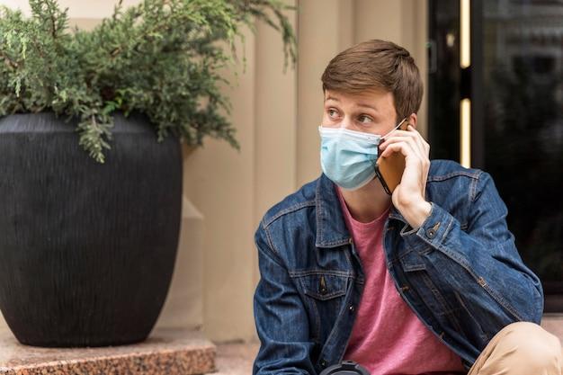 Mężczyzna ubrany w maskę podczas rozmowy przez telefon z miejsca na kopię