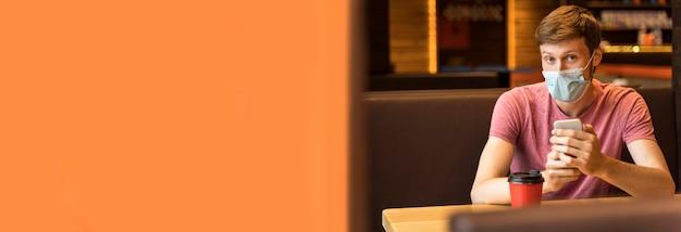 Mężczyzna ubrany w maskę w kawiarni z miejsca na kopię