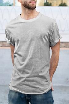 Mężczyzna ubrany w minimalną szarą koszulkę z modą odzieżą na świeżym powietrzu