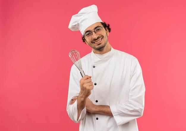 Mężczyzna ubrany w mundur szefa kuchni i okulary trzymając trzepaczkę na różowym tle