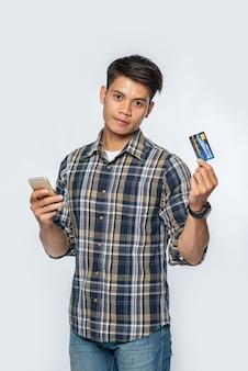 Mężczyzna ubrany w pasiastą koszulę trzyma kartę kredytową i smartfon