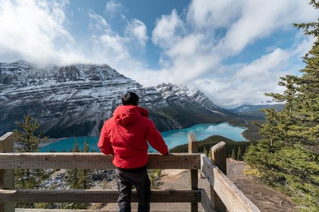 Mężczyzna ubrany w płaszcz zimowy stojący i patrząc widok na jezioro peyto w parku narodowym banff