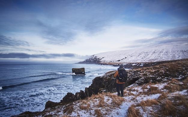 Mężczyzna ubrany w plecak i kurtkę stojący na zaśnieżonym wzgórzu podczas robienia zdjęcia morza