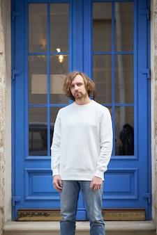 Mężczyzna ubrany w pustą białą bluzę. bluza lub bluza z kapturem do tworzenia makiet, projektów logo lub nadruku z wolnym miejscem.