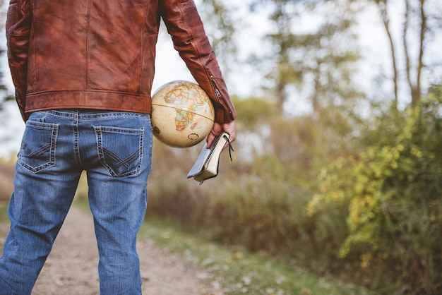 Mężczyzna ubrany w skórzaną kurtkę i dżinsy, trzymając kulę biurkową i biblię