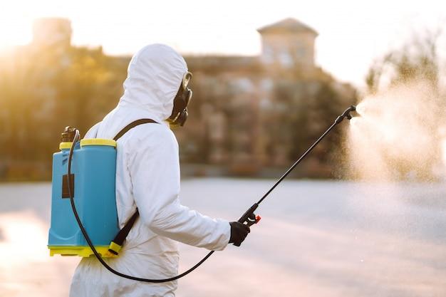 Mężczyzna ubrany w specjalny strój ochronny do dezynfekcji rozpyla sterylizator w pustym miejscu publicznym o świcie w mieście kwarantanny. covid 19. koncepcja czyszczenia.