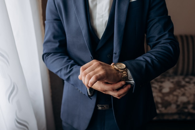 Mężczyzna ubrany w stylowy niebieski garnitur, który zakłada elegancki zegarek