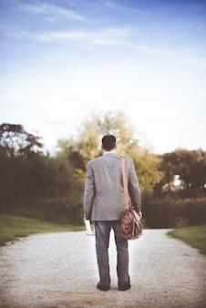 Mężczyzna ubrany w szary płaszcz stojący w pobliżu drogi w ciągu dnia