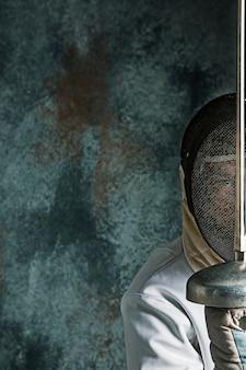 Mężczyzna ubrany w szermierkę z mieczem na szaro