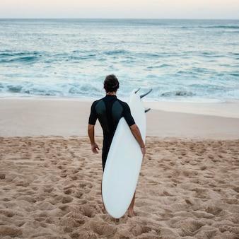 Mężczyzna ubrany w ubrania surfera chodzenia po piasku od tyłu