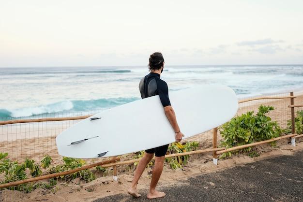 Mężczyzna ubrany w ubrania surferów i trzymając jego deskę surfingową z daleka
