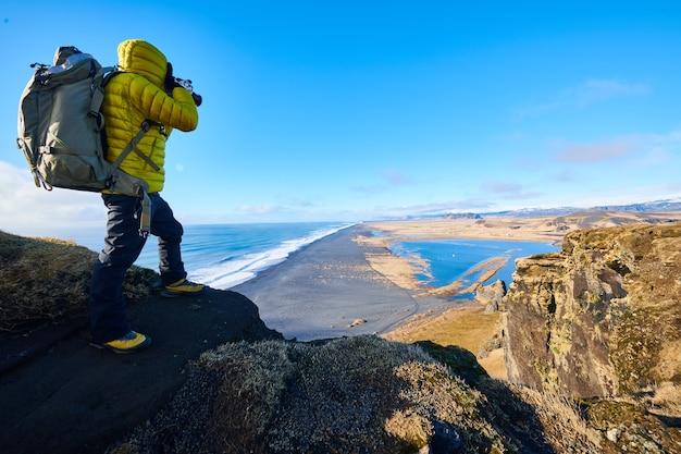 Mężczyzna ubrany w żółtą kurtkę stojący na skale podczas robienia zdjęcia pięknej scenerii