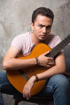Mężczyzna ubrany w zwykłą koszulę na krześle trzymając gitarę.